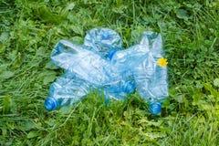 Пластичные бутылки минеральной воды на траве в парке, засаривать окружающей среды Стоковая Фотография
