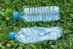 Пластичные бутылки минеральной воды на траве в парке, засаривать окружающей среды Стоковое фото RF