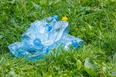 Пластичные бутылки минеральной воды на траве в парке, засаривать окружающей среды Стоковые Фотографии RF