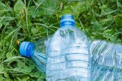 Пластичные бутылки минеральной воды на траве в парке, засаривать окружающей среды Стоковые Изображения RF