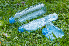 Пластичные бутылки минеральной воды на траве в парке, засаривать окружающей среды Стоковые Фото