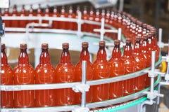 Пластичные бутылки при пиво или carbonated напиток двигая дальше транспортер Стоковое Изображение RF