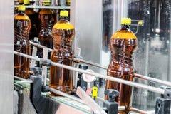 Пластичные бутылки с пивом на транспортере Стоковая Фотография RF