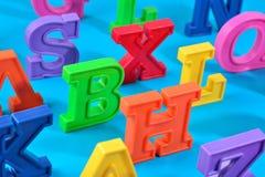Пластичные красочные письма алфавита закрывают вверх на сини Стоковые Фотографии RF