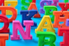 Пластичные красочные письма алфавита закрывают вверх на сини Стоковое фото RF
