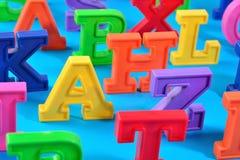 Пластичные красочные письма алфавита закрывают вверх на сини Стоковая Фотография RF