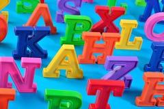 Пластичные красочные письма алфавита закрывают вверх на сини Стоковые Изображения RF