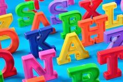 Пластичные красочные письма алфавита закрывают вверх на сини Стоковые Фото