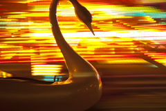 Пластичный лебедь на веселом идет круг с запачканной покрашенной предпосылкой стоковая фотография