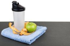 Пластичный шейкер, яблоко, лента измерений на голубом полотенце на циновке Стоковое Изображение RF