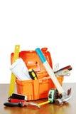 Пластичный toolbox с различными инструментами деятельности стоит на таблице Стоковые Изображения RF