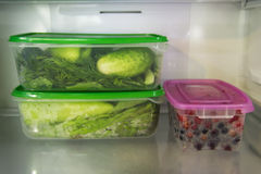 2 пластичных пищевого контейнера с зеленым овощем и один с ягодами на полке холодильника Стоковая Фотография