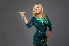 Платье вечера белокурой девушки нося выпивая Мартини стоковые фотографии rf