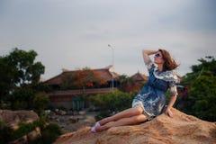 платье девушки брюнет вкратце серое сидит на утесе против вилл Стоковая Фотография RF