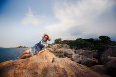 платье девушки вкратце серое лежит на утесе против заводов камней Стоковые Изображения RF