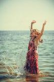 Платье девушки малыша нося играя в воде Стоковое Фото