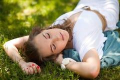 Платье девушки нося белое вне в парке лежа на траве Стоковые Изображения