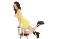 Платье женщины желтое короткое вставать на стуле Стоковое Изображение