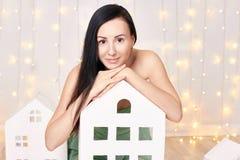 Платье зеленого цвета брюнет вкратце представляя в студии около домов игрушки ` s детей Красивая привлекательная девушка на предп Стоковое Изображение
