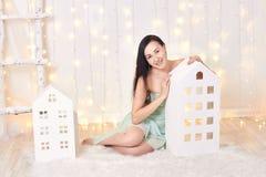 Платье зеленого цвета брюнет вкратце представляя в студии около домов игрушки ` s детей Красивая привлекательная девушка на предп Стоковые Фото