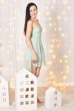 Платье зеленого цвета брюнет вкратце представляя в студии около домов игрушки ` s детей Красивая привлекательная девушка на предп Стоковые Изображения RF