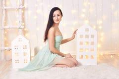 Платье зеленого цвета брюнет вкратце представляя в студии около домов игрушки ` s детей Красивая привлекательная девушка на предп Стоковая Фотография RF