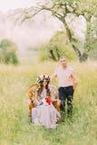 Платье и венок сирени красивой женщины нося держа букет сидя в стуле при красивый человек стоя близко Стоковые Фото
