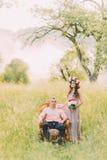 Платье и венок сирени красивой женщины нося держа букет стоя около красивого человека сидя в стуле outdoors Стоковое Изображение RF