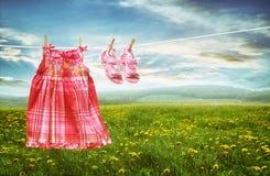 Платье и сандалии на веревке для белья в полях одуванчиков Стоковая Фотография RF