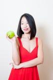 Платье молодой красивой азиатской женщины красное смотря зеленое яблоко Стоковое Изображение