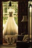 Платье свадьбы вися над окном Стоковое Изображение RF