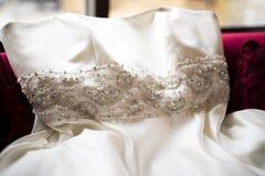 Платье свадьбы положенное на красное кресло бархата Стоковая Фотография