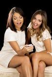 2 платья женщин белых сидят телефон счастливый стоковое фото