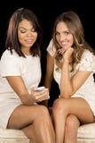 2 платья женщин белых сидят улыбка телефона одного стоковая фотография