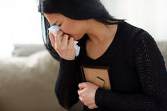Плача женщина с рамкой фото на похоронном дне стоковое фото rf