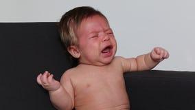 Плача младенец сидя с белой предпосылкой видеоматериал