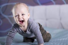 Плача счастливый ребёнок на кровати Смеясь над ребенк малыша смотря камеру Вползая младенец в его комнате стоковое изображение