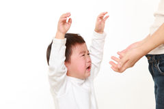 Плача японский мальчик который держится ее матерью Стоковая Фотография RF