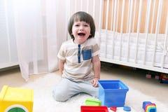 Плачущ 2 года мальчика разбрасывает игрушки дома Стоковое Изображение RF