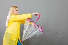 Плащ женщины нося держа зонтик стоковое изображение rf