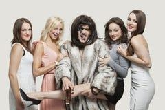 Плейбой с красивыми женщинами над серой предпосылкой стоковая фотография