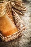 Плетеная корзина отрезала уши пшеницы хлеба здравицы на предпосылке мешковины Стоковые Фотографии RF