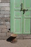 Плетеный стул и зеленая дверь Стоковые Изображения