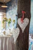 2 плетеных сердца вися на дереве Стоковые Изображения