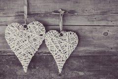 2 плетеных сердца вися на деревянной предпосылке Стоковое Изображение