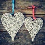 2 плетеных сердца вися на старой деревянной стене Стоковое Изображение