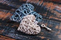 2 плетеных сердца и ключ на затрапезной предпосылке Стоковая Фотография RF