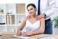 Плечи бизнесмена касающие его милого коллеги на рабочем месте Стоковое Фото