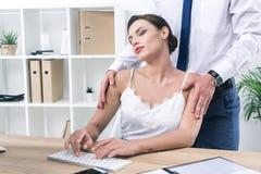 Плечи бизнесмена касающие его милого коллеги работая с ПК Стоковое Изображение