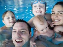 плечо бассеина отцов семьи дочи счастливое сидит Стоковая Фотография